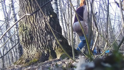 beautiful red-haired girl pissing near a tree
