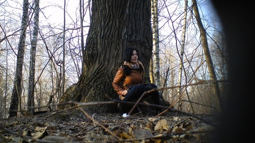 beautiful brunette in jeans pisses near a tree