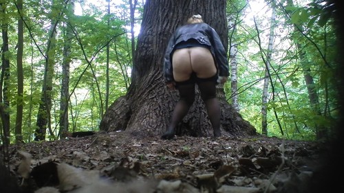 blonde woman in a blue skirt pisses near a tree