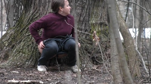 plump woman pisses near a tree