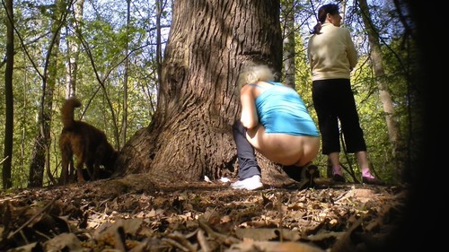 two adult women pisses around a tree