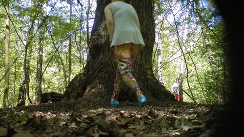 woman in bright pants pisses near a tree