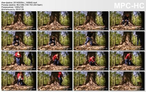 two adult women in jeans pissing near a tree