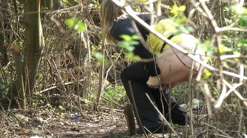 young blonde woman pissing in bushes
