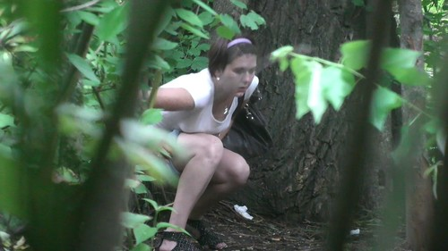 girl in shorts and a white T-shirt pissing in the woods