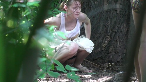 woman in a white skirt pissing in the woods