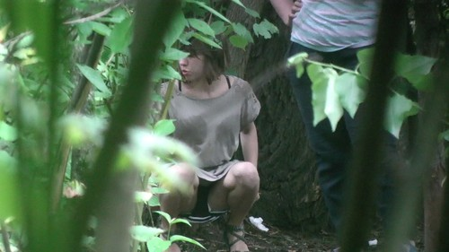 girl in gray dress pissing in the woods