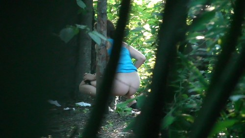 girl in a blue T-shirt pissing in the woods