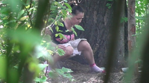 girl in light shorts pissing in the woods