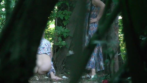 a group of women pissing in the bushes